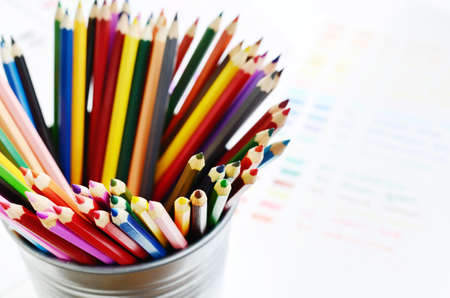 Set of multicolored wooden pencils in metal holder and color palette photo
