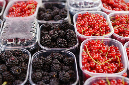 plastic to containers: Blackberry and red currant in plastic containers at the market