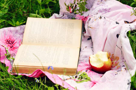 biten: Picnic in green grass apple and open book over bright florish babydoll