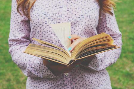 mujer leyendo libro: Mujer joven que sostiene el libro abierto en sus manos, el verano de fondo