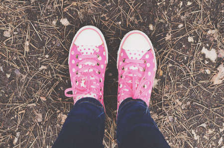 young girl feet: Pink polka dot trainers and woman legs in jeans