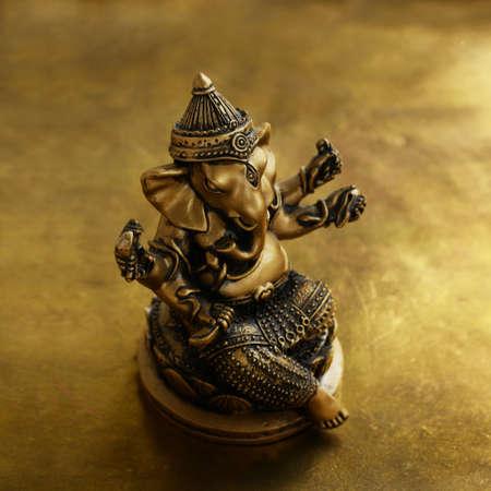 ganapati: Ganesha bronze statuette over golden background, square