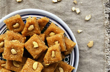 indian sweet: Homemade burfi - traditional indian sweets made of milk, chickpea flour, coconut flakes, cardamom and cashew nut Stock Photo