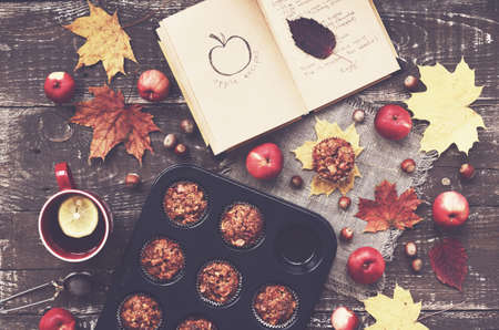 mood: Cozy autumn breakfast - homemade apple muffins and cup of tea with lemon, top view Stock Photo
