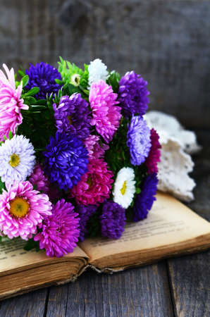 flores moradas: Bunch of colorful aster flowers over vintage book with copy space wooden background Foto de archivo