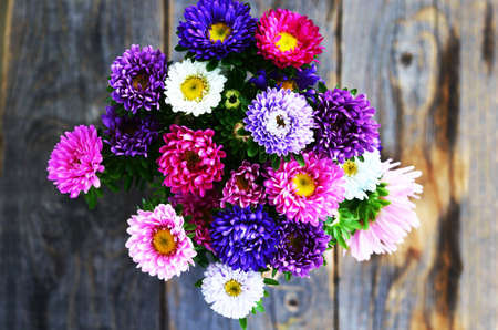 flower arrangements: Bouquet of pink, violet and white aster over wooden background, top view