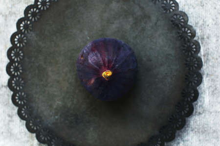 purple fig: Single purple fig on rustic metal plate, top view Stock Photo