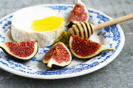 brie: Brie cheese, honey and fig on blue ceramic plate Stock Photo