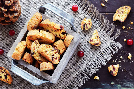 biten: Cranberry biscotti in decorative crate on linen napkin on rusted wooden table