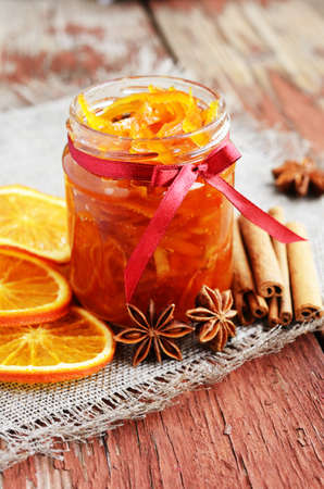peels: Homemade candied peels orange confiture in glass jar with spices - cinnamon and anise star on rusted wooden background