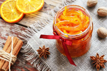 naranja color: Homemade candied peels orange confiture in glass jar with spices - cinnamon, nutmeg and anise star on rusted wooden background Foto de archivo