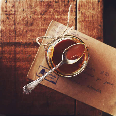 caramel sauce: Homemade salted caramel sauce in glass jar on wooden background, table top