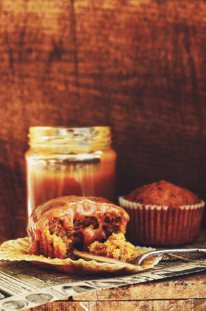 caramel sauce: Homemade carrot muffins and caramel sauce on wooden background Stock Photo