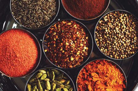 especias: Estante con especias tradicionales indios para cocinar - cardamomo verde, cúrcuma en polvo, semillas de cilantro, canela, comino y ají