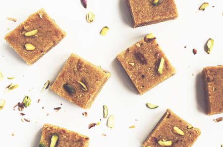 indian sweet: Homemade besan coconut burfi, traditional indian sweet made of chickpeas flour, coconut flakes, ghee butter, cardamom and pistachio