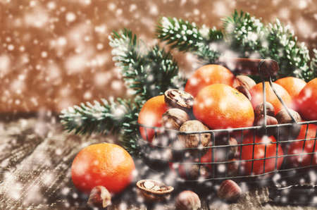 hazelnut tree: Christmas decoration with ripe tangerines in wire basket, walnut, hazelnut,  pine tree twigs and snowflakes with copy space on wooden background