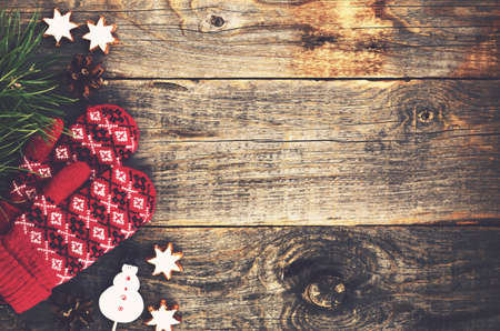 Red knitted mittens and christmas toys with empty space on wooden background