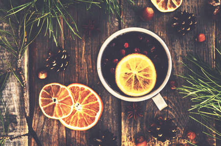 winter trees: Winter drink with lemon, cranberries and spices on wooden background, top view