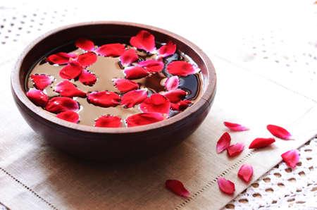 リラクゼーションのための赤のバラの花びらを浮動素朴な木製ボウル