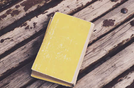 rusted background: Yellow retro book on wooden rusted background Stock Photo