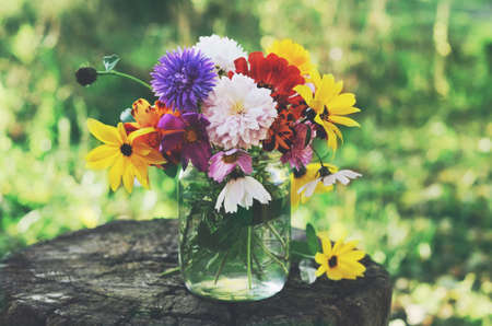 Bunch of flowers in glass jar on tree stub, summer background