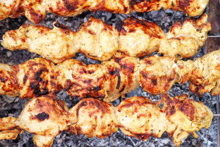 Shish kebab close-up  Slices of meat in marinade preparing on fire  photo