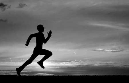Silhouette of running man on sunset  Standard-Bild
