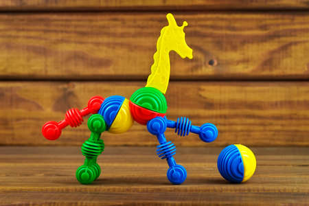 Toy giraffe and ball made from plastic colorful details on wooden background. Giraffe play with a ball.  photo