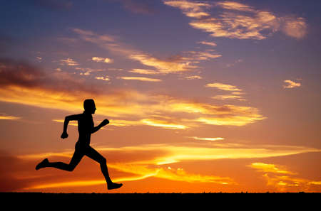 man power: Silhouette of running man against the colorful sky. Silhouette of running man on sunset fiery background