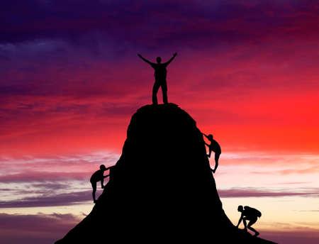 Man on top of the mountain and the other people to climb up on fiery orange background.  photo