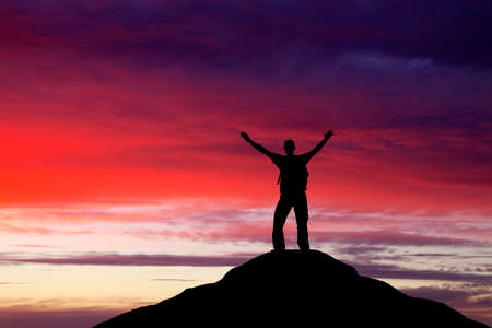 Silhouette of a man on a mountain top. Person silhouette on the rock. Sport and active life concept  Standard-Bild