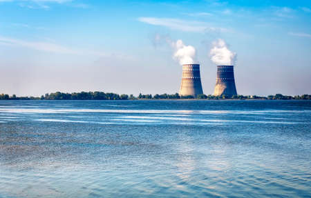 cooling towers: Cooling towers with steam from a nuclear power station on a river