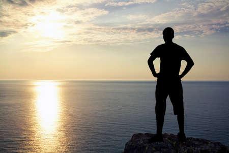 夕暮れ時の岩の上の人間のシルエット。山の頂上に男。概念設計。 写真素材