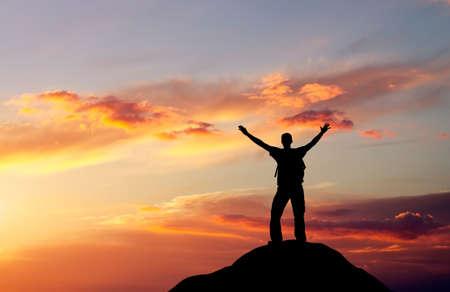 Silhouet van een man op een bergtop op vurige oranje achtergrond Stockfoto