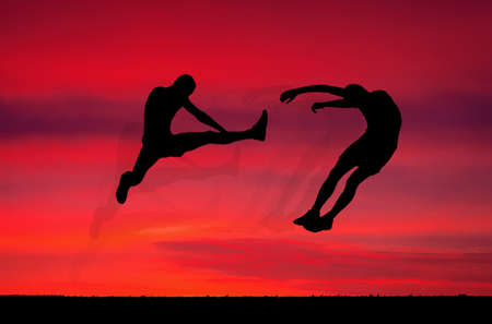 opponents: Silhouettes of two fighters on sunset fiery . Battle at sunset. Kick in the air at the opponents body. Stock Photo