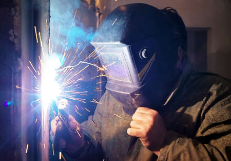 welding mask: Worker with protective mask welding metal and sparks