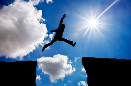 El hombre que salta a través del hueco de una roca a aferrarse a la otra. El hombre que salta sobre las rocas con la brecha en el atardecer de fondo ardiente. Elemento de diseño. Foto de archivo