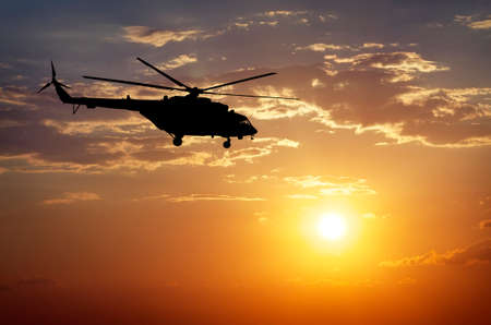 helicopter: Picture of helicopter at sunset. Silhouette of helicopter on sunset sky. Stock Photo