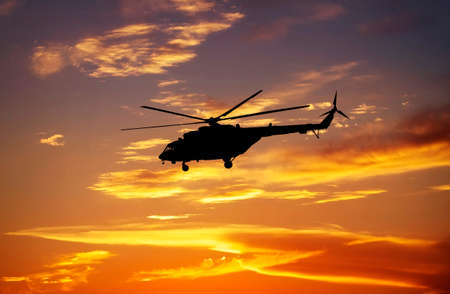 Picture of helicopter at sunset. Silhouette of helicopter on sunset sky. Stock Photo