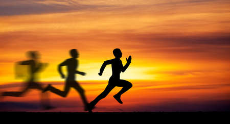 races: Silhouette of running man against the colorful sky. Silhouette of running man on sunset fiery background