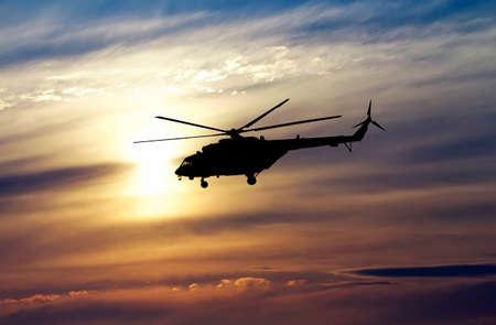 夕暮れ時のヘリコプターの画像。夕焼け空にヘリコプターのシルエット。