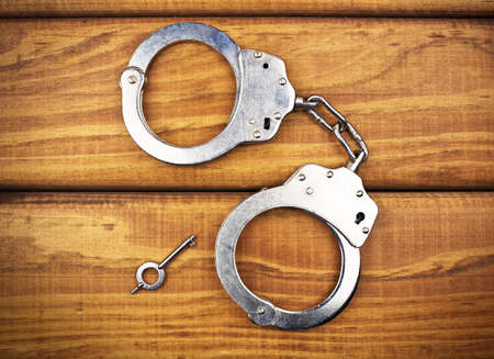 restraints: Steel metallic handcuffs on a wooden table Stock Photo