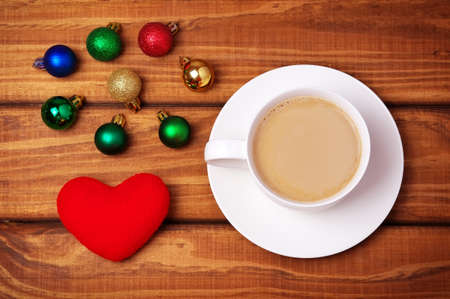 christmas bubbles: Cup of coffee, heart and christmas bubbles on wooden background. Stock Photo