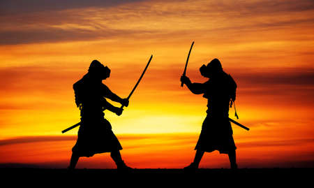 ninja: Silhouette of two samurais in duel. Picture with two samurais and sunset sky