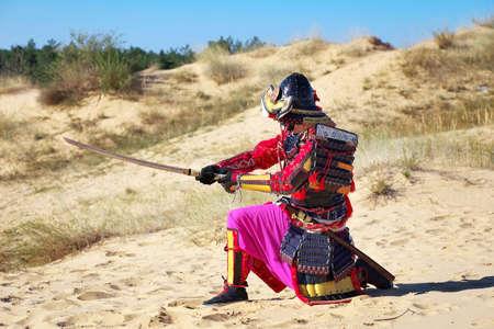 samourai: Samurai avec l'�p�e sur le sable. Les hommes en armure de samoura� sur le sable. Le caract�re original