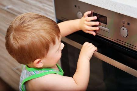 台所で危険な状況。電気オーブンと遊ぶ子供。