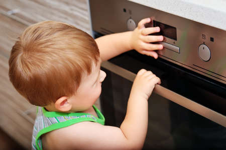 curious: Dangerous situation in the kitchen. Child playing with electric oven. Stock Photo