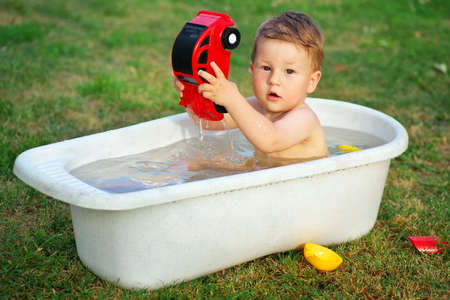 bathed: A small baby bathed in the bath and playing with toy car.