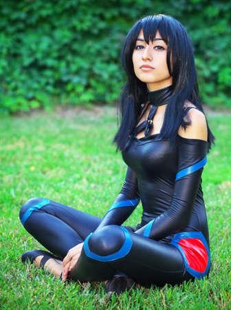 草の上に座っている若い女の子。オリジナルのコスプレ キャラクター
