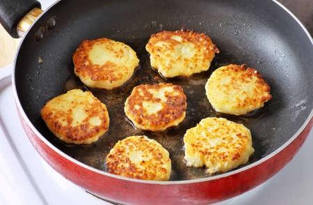 queso: Hermosas tortitas de queso de oro fr�en en una sart�n. Syrniki. Panqueques queso cottage. Bu�uelos de queso cottage, Ucraniano plato tradicional y la cocina rusa.